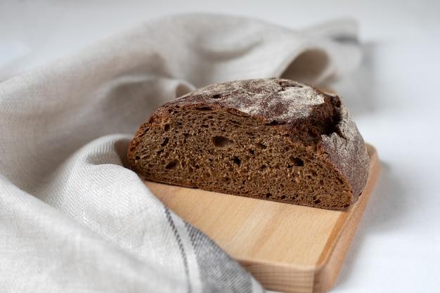 Tagliare il pane di segale nero su una tavola di legno