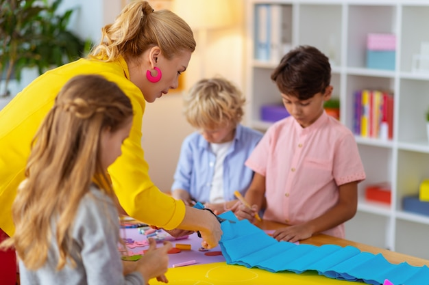 Taglia la carta blu. insegnante che indossa una giacca gialla che aiuta gli alunni a tagliare la carta blu per l'ornamento applicato