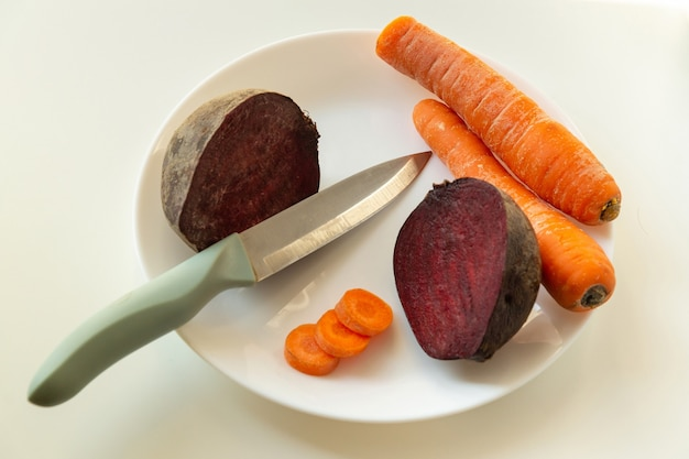 Tagliare le carote e le barbabietole con un coltello nella piastra prima della cottura. idea per la dieta o il digiuno
