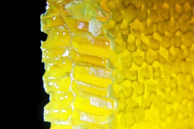 Il miele di favo tagliato si illumina su uno sfondo nero. cibo vitaminico utile