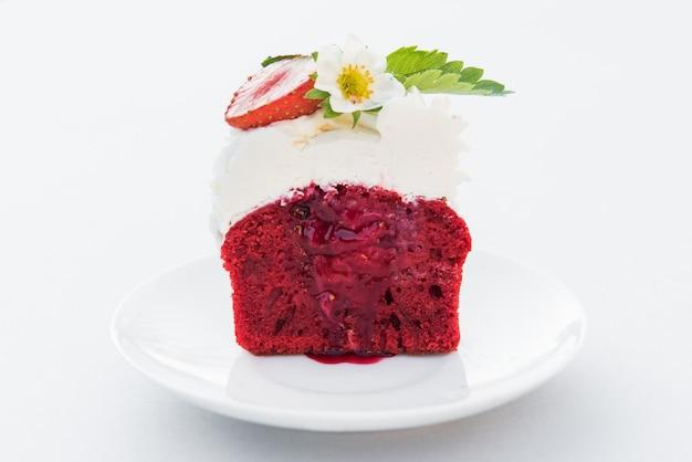 Tagli il velluto rosso del bigné con la fragola e la crema sul piatto bianco. avvicinamento