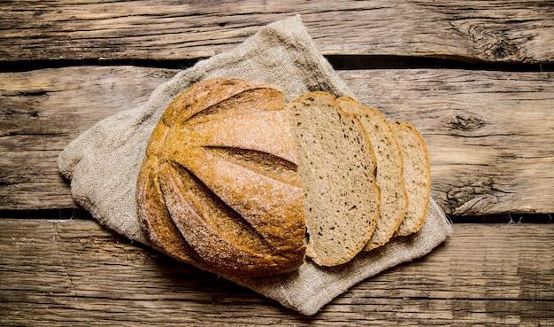 Taglia il pane fresco su un vecchio tessuto. sul tavolo di legno.