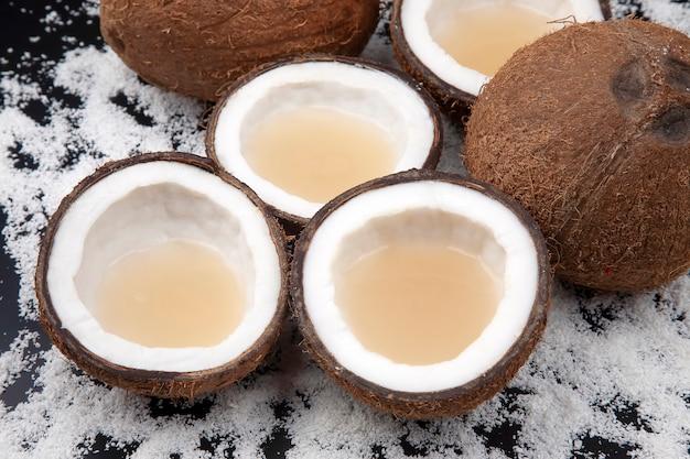 Taglia il cocco fresco con vero latte di cocco su uno sfondo di fiocchi di cocco. frutti vitaminici. cibo salutare