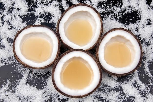 Taglia il cocco fresco con vero latte di cocco su uno sfondo di fiocchi di cocco. frutti vitaminici.