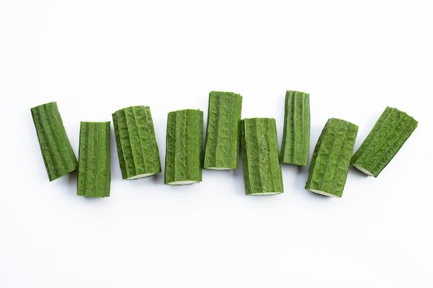 Tagliare le verdure fresche di luffa su sfondo bianco.