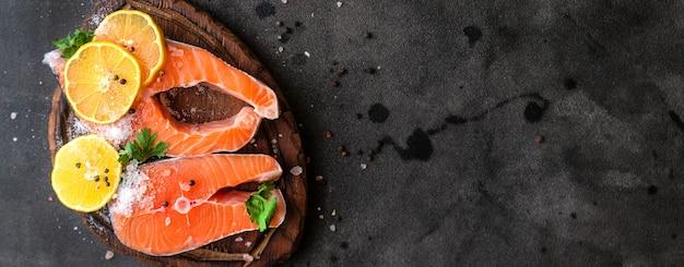 Tagliare il salmone crudo fresco della bistecca sull'insegna del bordo di legno