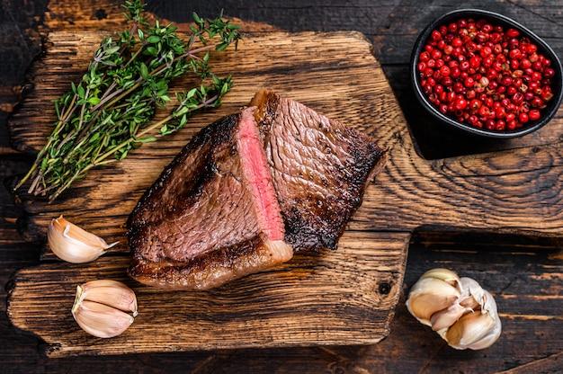 Tagliare il tappo di fesa fritto o bistecca di carne di manzo brasiliana picanha su una tavola di legno sul tavolo di legno. vista dall'alto.