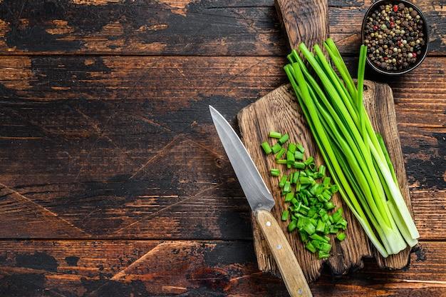 Tagliare l'erba cipollina delle cipolle verdi su un tagliere. fondo in legno scuro. vista dall'alto. copia spazio.