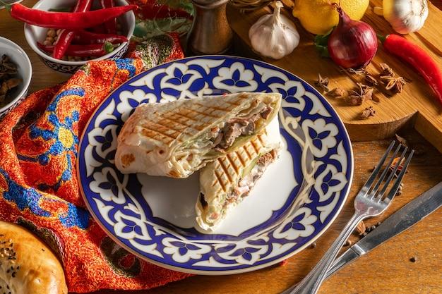 Tagliare a metà shawarma con carne di manzo su un piatto con un motivo uzbeko. piatto orientale caldo di verdure e carne avvolto nel pane pita.