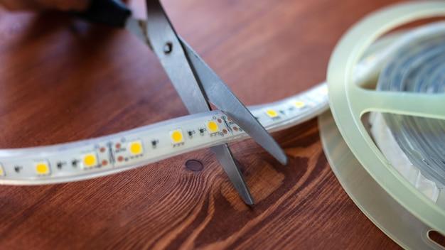 Tagliare la striscia led con le forbici in primo piano.