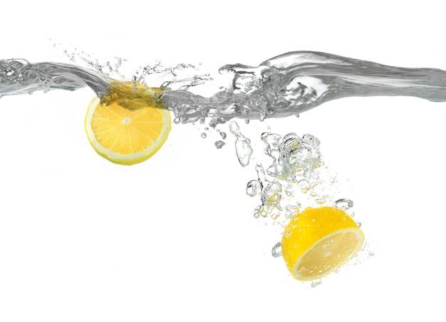 Il limone tagliato cade nell'acqua