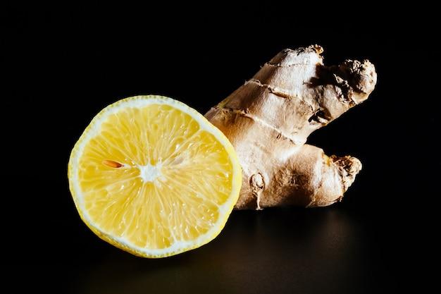 Tagliare il limone e lo zenzero isolati su una superficie nera, primo piano. ingredienti utili e vitamine naturali.