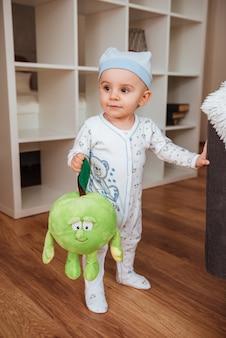 Taglia il ragazzino con il cappello in piedi e tiene il suo giocattolo a casa
