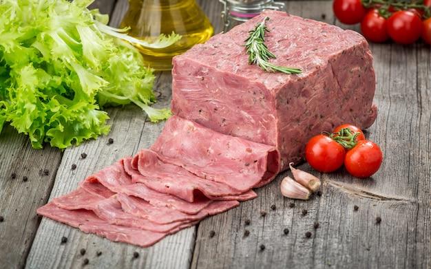 Tagliare la carne su una superficie di legno