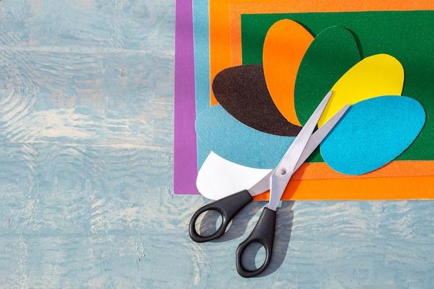 Ritagliare le uova di pasqua colorate, il modello e le forbici su carta colorata su un tavolo in legno blu, copia spazio, vista dall'alto, piatto laici. mestieri di carta creativi fai-da-te per pasqua.