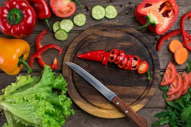 Tagliare il pepe su una tavola di legno e le verdure su un tavolo. copia spazio. vista dall'alto