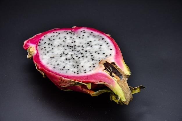Taglia la pitahaya sulla superficie nera da vicino, taglia il frutto del drago