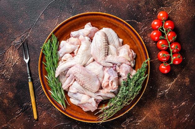 Tagliare le ali di pollo crude in un piatto rustico con timo e rosmarino. sfondo scuro. vista dall'alto.