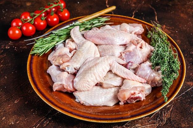 Tagliare alette di pollo crude in un piatto rustico con timo e rosmarino