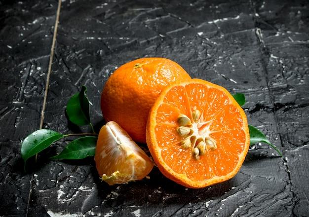Taglia il mandarino maturo con le foglie. su fondo rustico