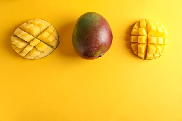Taglia i manghi maturi e lo spazio per il testo su sfondo colorato, vista dall'alto