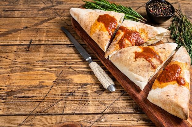 Tagliata e affettata calzone pizza chiusa con prosciutto e formaggio su tavola di legno con salsa di pomodoro piccante. fondo in legno. vista dall'alto. copia spazio.