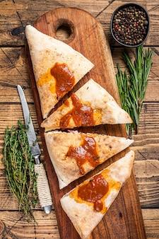 Tagliata e affettata calzone pizza chiusa con prosciutto e formaggio su tavola di legno con salsa di pomodoro piccante.