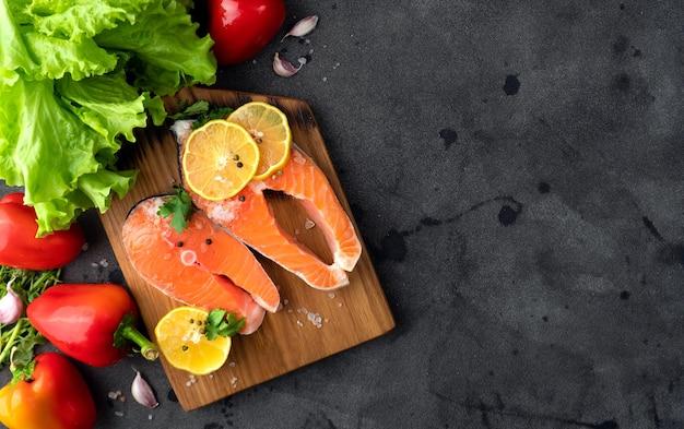 Tagliare il salmone della bistecca sul banner della tavola di legno