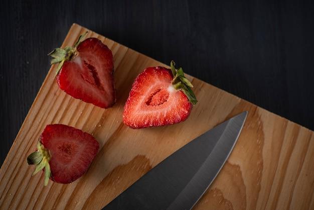Tagliare le fragole su una tavola di legno con un coltello a lato
