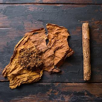 Tagliare tabacco e foglie di tabacco con sigaro su legno