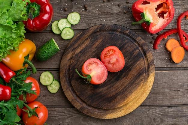 Tagliare il pomodoro su una tavola di legno e le verdure su un tavolo. copia spazio. vista dall'alto