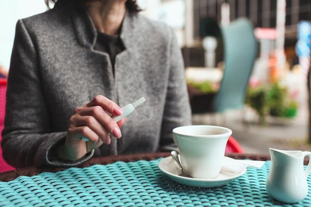 Vista in taglio della donna d'affari si siede da sola al tavolo del bar tenendo in mano la sigaretta elettronica