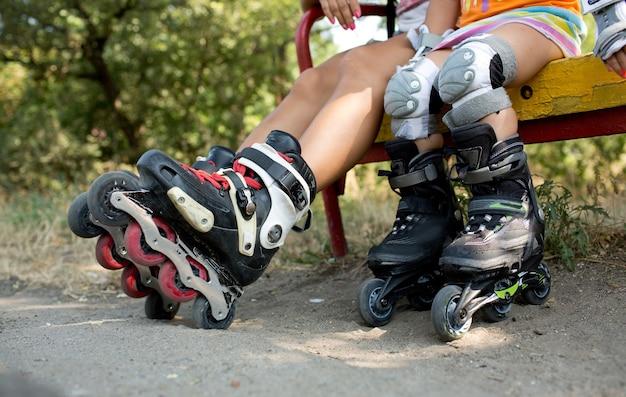 Vista in taglio delle gambe dei bambini con i rulli. i bambini si siedono sulla panchina all'esterno e riposano dopo aver pattinato. due bambini con il ginocchio e senza. protezione. luce solare fuori
