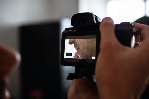 Vista in taglio e primo piano delle mani del cameraman che regolano la telecamera. registrare un video o scattare una foto del viso di un giovane impegnato.