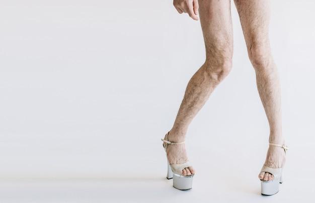 Vista in taglio di lunghe gambe curve in scarpa da donna bianca su tacchi alti.