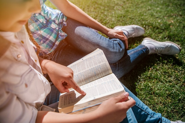 Vista in taglio della piccola ragazza seduta con un adulto sull'erba
