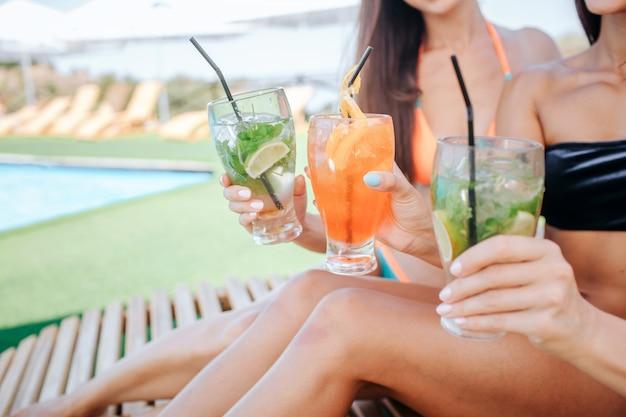 Tagliare la vista di tre belle donne sedersi sui lettini e tenere cocktail in mano. ci sono due verdi e uno arancione. le modelle incoraggiano il relax e il buon riposo.