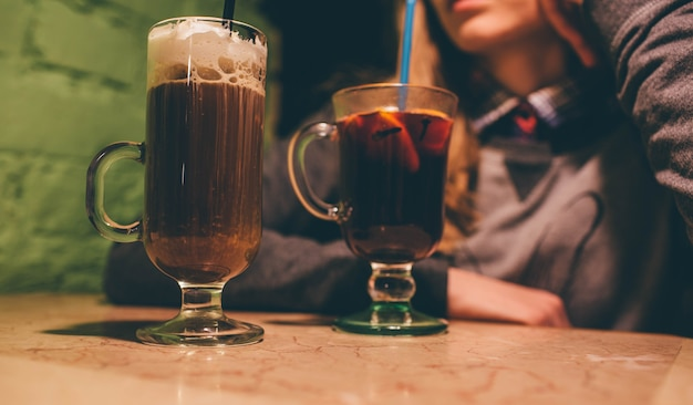 Vista in taglio della donna che si siede sul tavolo. latte con panna montata e vin brulè in bicchieri.