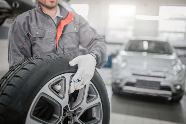 Tagli il punto di vista dell'operaio nel supporto dell'uniforme grigia e tenga la ruota di automobile con entrambe le mani.