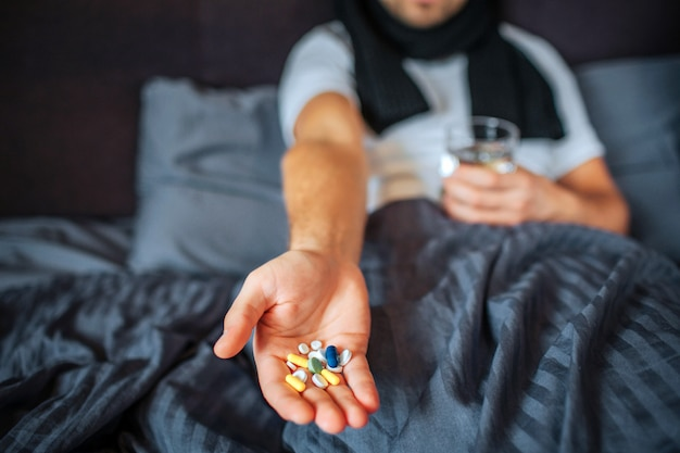 Tagli il punto di vista del giovane che si siede sul letto e che tiene un sacco di pillole a disposizione. guy ha anche un bicchiere d'acqua. l'uomo malato ha una sciarpa intorno al collo.