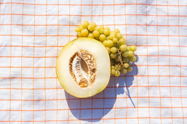 Tagliare il melone giallo, uva su una tovaglia sulla spiaggia. vista dall'alto, piatto.