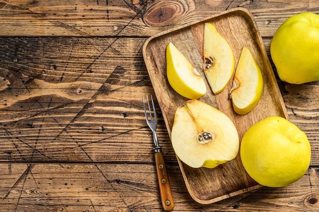 Tagliare i frutti di mela cotogna gialla in un vassoio di legno. fondo in legno. vista dall'alto. copia spazio.