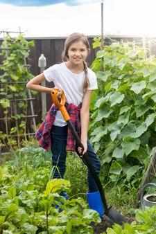 Carina ragazza di 10 anni che lavora in giardino e scava il terreno con la pala