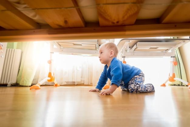 Simpatico bambino di 9 mesi che striscia sul pavimento di legno in camera da letto