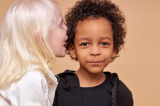 Bambini diversi adorabili svegli che sorridono insieme isolati