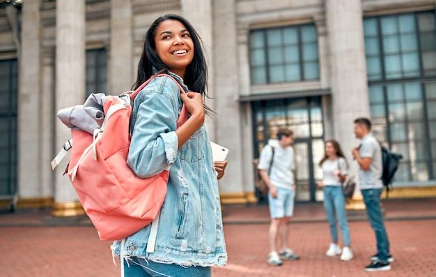 Una studentessa carina afroamericana con uno zaino rosa e un laptop sullo sfondo di un gruppo di studenti vicino al campus.