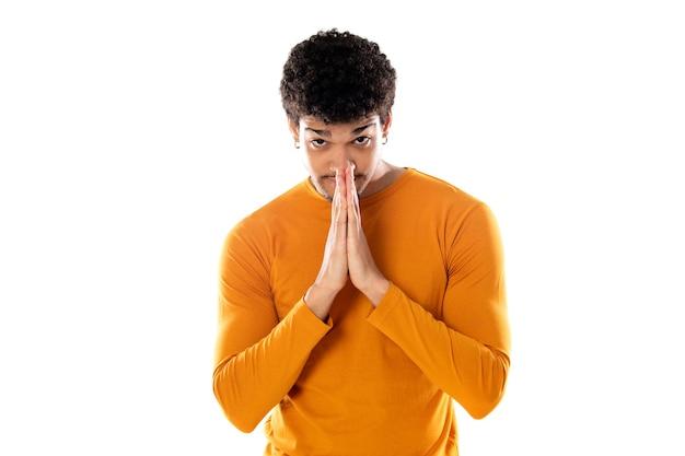 Uomo afroamericano sveglio con l'acconciatura afro che indossa una maglietta arancione isolata