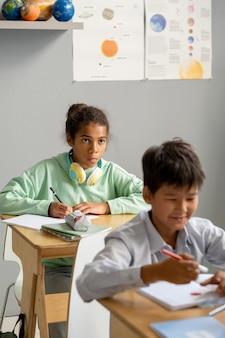 Carina studentessa afro-americana che guarda la lavagna o l'insegnante a lezione