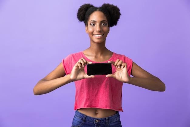 Carino donna afro-americana sorridente e tenendo il telefono cellulare, isolato