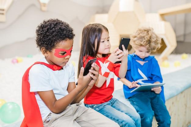 Ragazzo africano sveglio in costume del supereroe e dei suoi due amici che utilizzano gadget nel tempo libero mentre giocano o guardano cartoni animati